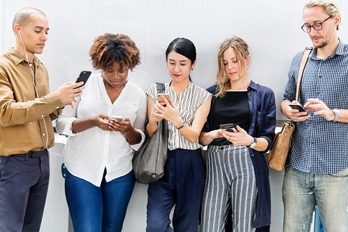 group of people standing on mobile phones addicted to phone not having conversation