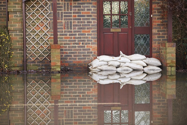 home emergency cover needed house flooded on outside with water damage sand bags lined up at front door